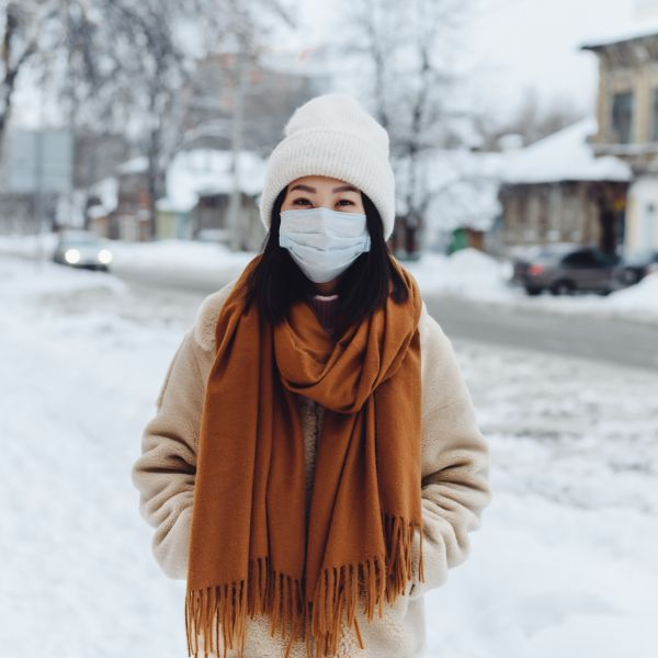 A person outside in the winter is wearing a face mask. They are bundled up with a hat and scarf and there is snow in the background. It's a quiet neighborhood street.