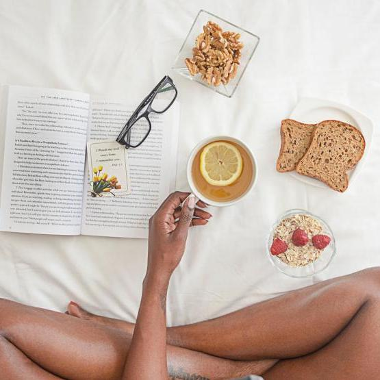 Person sitting on bed with book, tea, and glasses