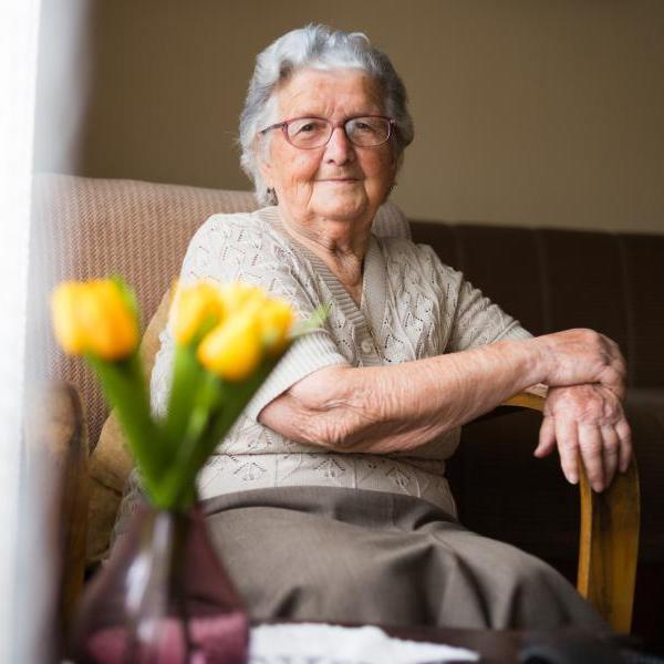 Older adult sitting in chair in room alone with slight smile.