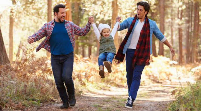 Couple walking through woods with daughter