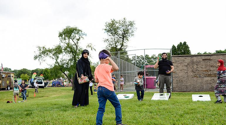 Family playing bag toss game at a park.