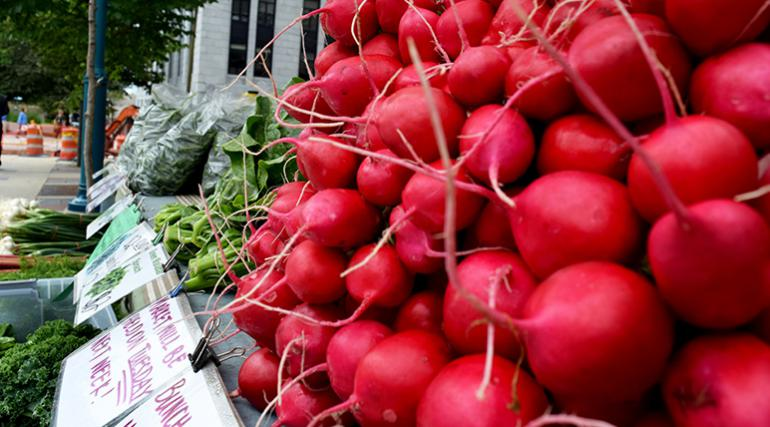 Radishes for sale at a road-side farmers' market stand.