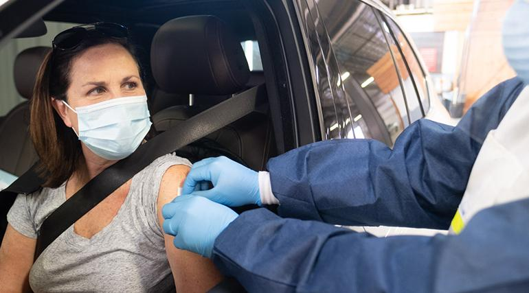 A masked woman in a vehicle getting prepped for vaccination by a health worker