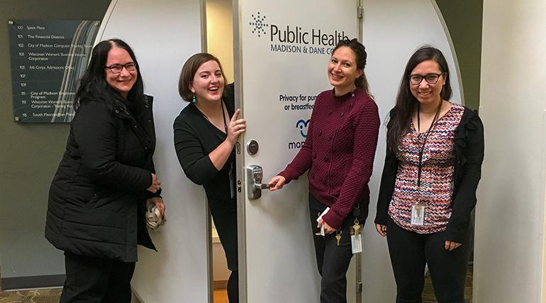 Public Health employees standing in front of a stand-alone breast feeding room.