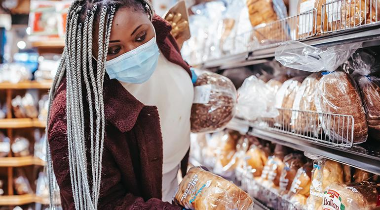 A masked woman shopping in a grocery store