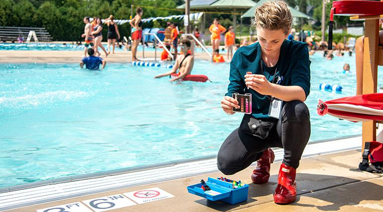 Woman poolside testing chemical levels of the water with swimmers in the background