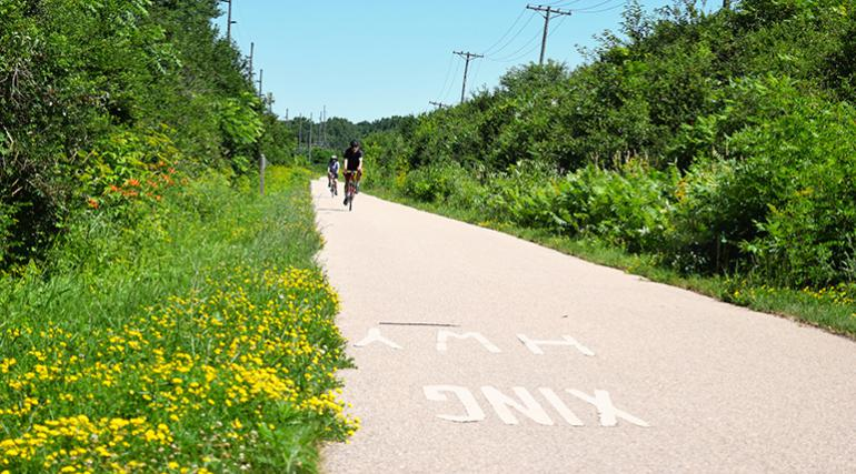 Two cyclists riding on a Madison, WI bike path.
