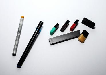 Three e-cigarettes and filters laying on a table