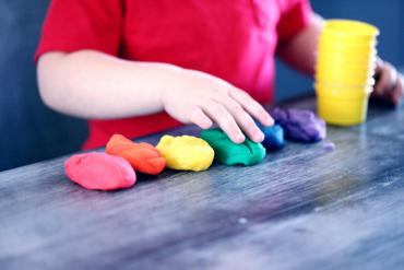 A child plays with colored clay at a childcare center